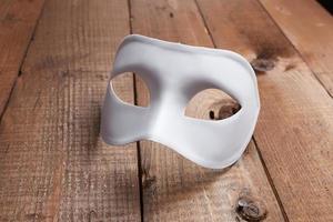 máscara veneziana branca em cima da mesa foto