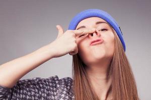 garota segurando os dedos no nariz e fazendo expressão boba