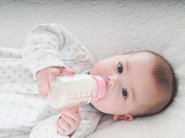 menino bebendo leite da garrafa em casa foto