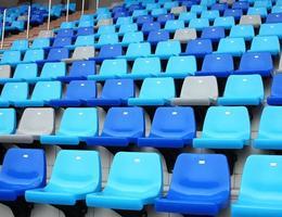 assentos de plástico velhos estádio azuis em degraus de concreto foto