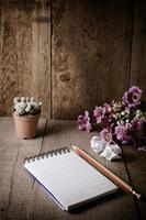 bloco de notas em branco com lápis na mesa de madeira foto