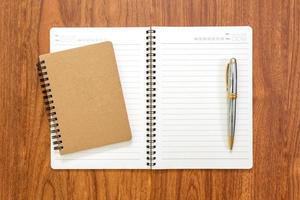 caderno em branco com uma caneta no fundo madeira foto