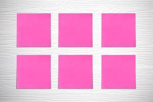 almofadas de nota rosa na parede branca de madeira foto