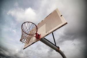 cesta de basquete ao ar livre e céu dramático foto