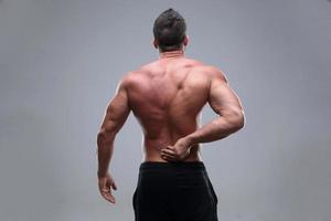 homem musculoso com dor nas costas foto
