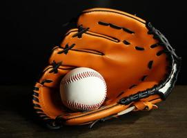 luva de beisebol e bola em fundo escuro foto
