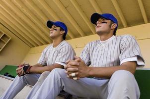 jogadores de beisebol em abrigo assistindo jogo foto