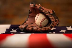 luva de beisebol sobre a bandeira americana