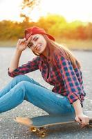 garota em uma camisa e um boné de beisebol ao pôr do sol