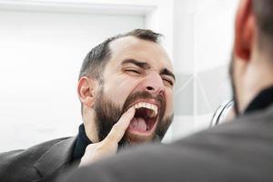 homem com dor de dente foto