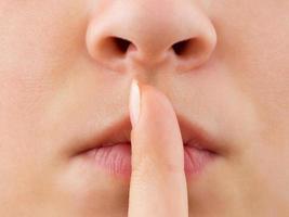 mulher segurando o dedo nos lábios foto
