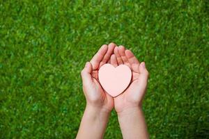 mãos humanas segurando coração foto