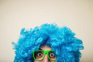 homem barbudo engraçado louco com peruca azul foto