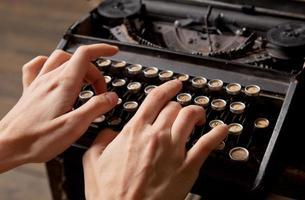 mão humana imprime na máquina de escrever retrô. foto