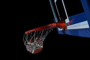 bola de basquete e net em fundo preto foto