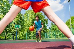 menino com bola vista entre duas pernas do jogador foto