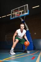 forte saudável jovem jogando basquete no ginásio interior. foto