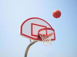 cesta e bola de basquete foto