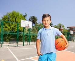 alegre rapaz segurando uma bola de basquete em uma quadra ao ar livre foto