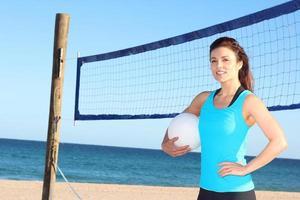 mulher em pé com uma bola de vôlei foto
