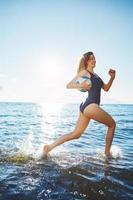jovem mulher correndo na água com vôlei foto