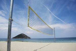 rede de vôlei de praia em uma praia arenosa foto