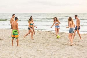 grupo de amigos jogando bola na praia foto