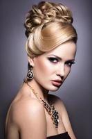 menina bonita com maquiagem brilhante e penteado de noite. foto