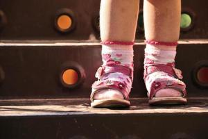pernas de bebê em sapatos e meias, em pé na escada