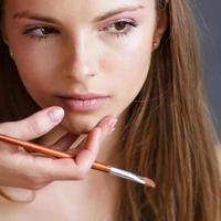 garota aplicando maquiagem pelo maquiador.