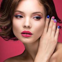 menina linda modelo com maquiagem rosa brilhante e unhas coloridas