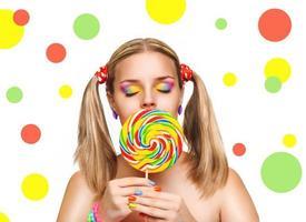 garota comendo pirulito colorido. pirulito. foto