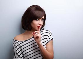 mulher bonita de cabelo curto maquiagem mostrando sinal de silêncio