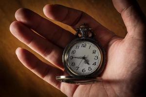 relógio de bolso na mão humana. foto