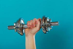 masculino mão segurando halteres pesados foto