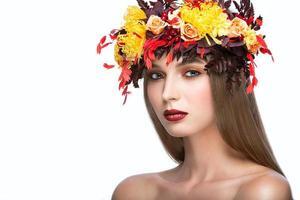 linda menina com coroa de outono brilhante de folhas e flores foto