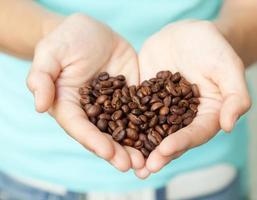 grãos de café em mãos humanas, em foco suave foto