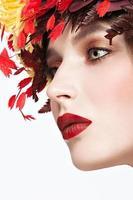linda garota ruiva com coroa de outono brilhante de folhas foto