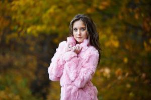 linda garota com um casaco de pele rosa