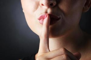 closeup foto de mulher fazendo um gesto de silêncio