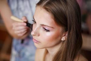 jovem loira aplicar maquiagem pelo maquiador.
