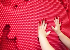 mãos de bebê fazendo impressão da mão no brinquedo pin vermelho