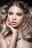 menina loira bonita com maquiagem de noite e penteado incomum