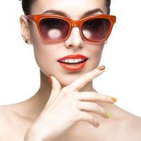 uma garota usando um óculos de sol vermelho e unhas coloridas foto