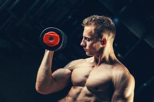 fisiculturista muscular atleta treinando de volta com halteres no ginásio foto