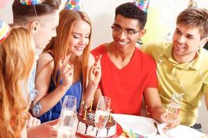 jovens comemorando um aniversário sentado à mesa