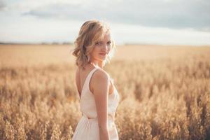 bela jovem no Prado de verão ao pôr do sol amarelo foto
