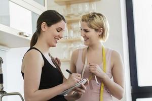 mulher anotando o peso do amigo em um notebook foto