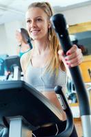 jovens com máquina elíptica no ginásio. foto