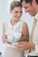 mulher de negócios atraente rindo com seu colega foto